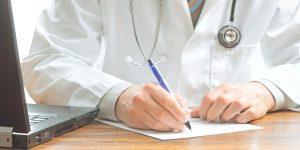 Врач пишет ручкой на бумаге